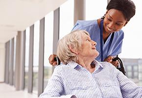 Elderly patient in a wheelchair with her nurse