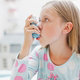 A child uses an inhaler for asthma