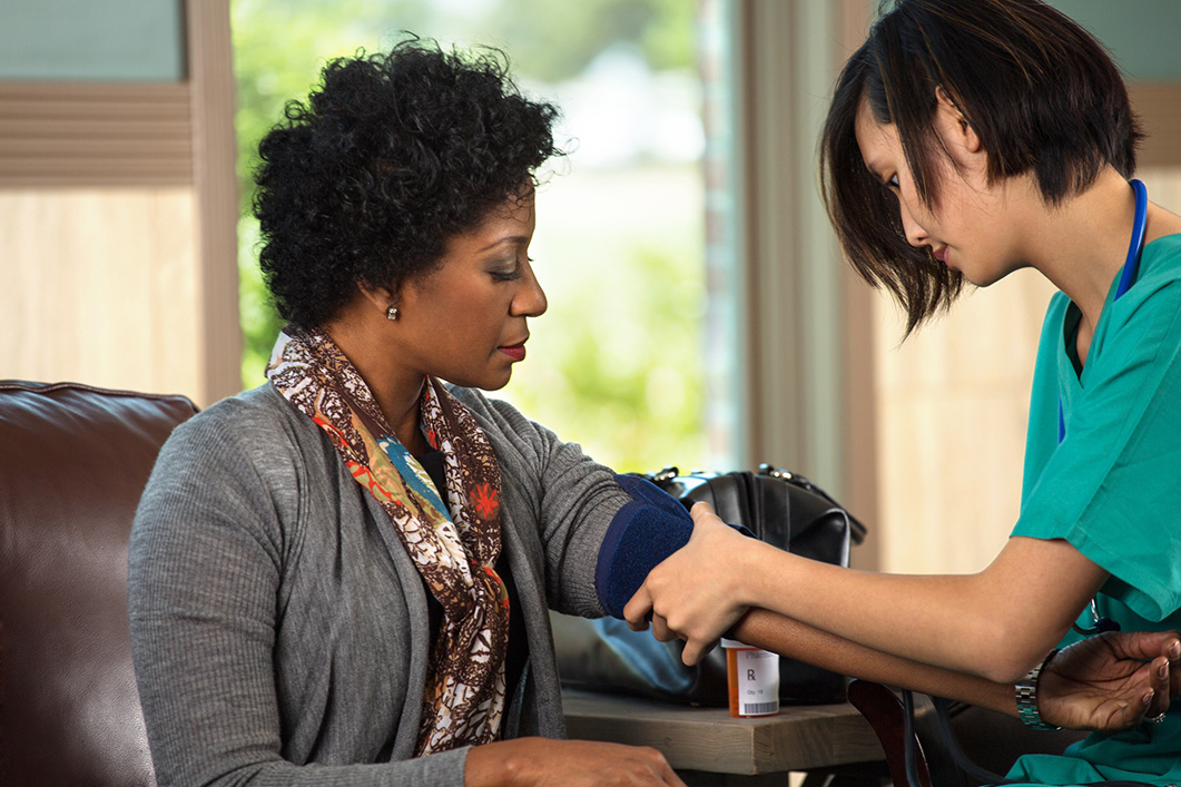 A nurse in a doctor's office taking the blood pressure of a seated African American female patient.