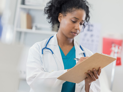 A doctor writes down information on a clipboard.