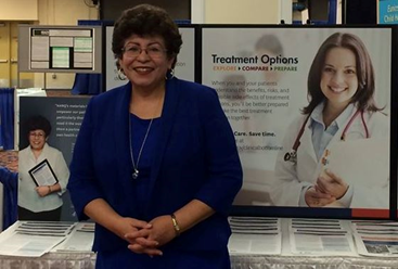 Elena Rios, M.D., M.S.P.H., president and CEO of the National Hispanic Medical Association, stands in front of an AHRQ exhibit booth.