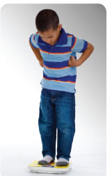 A photograph shows a little boy standing on a scale.