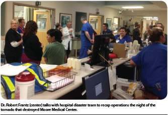 Dr. Robert Frantz (center) talks with hospital disaster team to recap operations the night of the tornado that destroyed Moore Medical Center.