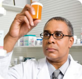 Photograph of a pharmacist holding up a prescription medication bottle.