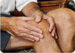 Photograph of two hands massaging a knee, captioned 'Osteoarthritis Pain'