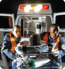 Photograph shows EMT personnel removing a patient on a stretcher from an ambulance.
