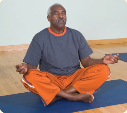 Photograph shows a man seated in a meditation position.