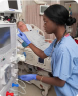 Photograph of a technician working with a dialysis machine.