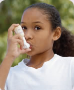 Photograph shows a little girl using an asthma inhaler.