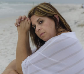A sad-looking woman sits on the beach.