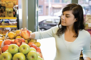 A woman is shown selecting apples at the supermarket.