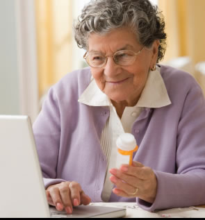 Photograph shows a woman looking for information about her medications on her laptop computer.
