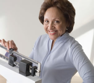 Photograph shows a smiling woman weighing herself.