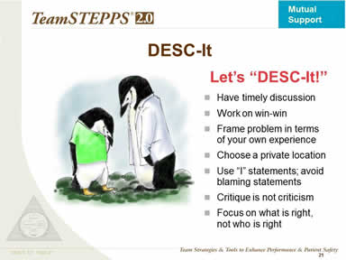 Text description is below the image. Image: Two penguins, one in white coat, have a quiet discussion.