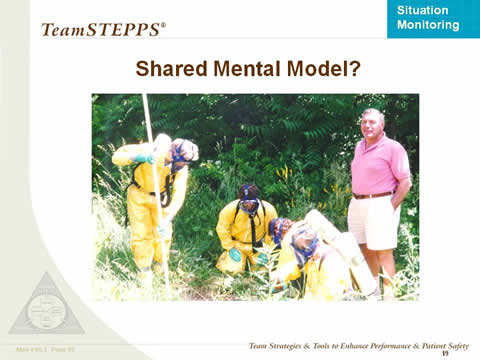 Shared Mental Model? Four people in a group are wearing hazard suits and masks and searching the ground. A fifth person in shorts and polo shirt stands by apparently unconcerned.