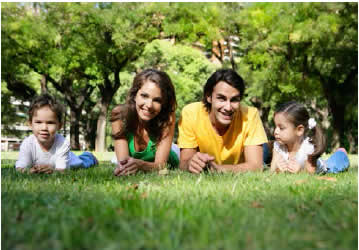 Photograph shows a happy family of two parents and two small children lying on the grass.