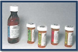 Photograph of a medication bottle and 4 pill containers.