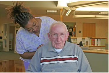 Photograph of staff member with nursing home resident.